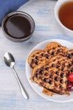 以心脏的形式甜比利时华夫饼干用巧克力和莓果在蓝色木背景 早餐 免版税库存图片