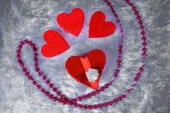 以心脏的形式礼物盒栓与与弓的一条红色丝带以玫瑰的形式是一张装饰涂层ametiruum毛皮 免版税库存照片