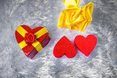 以心脏的形式礼物盒栓与与弓的一条黄色丝带以玫瑰的形式在枕头伪造品毛皮说谎和其次 库存图片