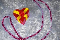 以心脏的形式礼物盒栓与与弓的一条黄色丝带以玫瑰的形式是一张装饰涂层ametiruum毛皮 免版税库存图片