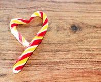 以心脏的形式糖果在华伦泰` s天的庆祝的木背景 心脏是残破的 欺诈 免版税库存图片