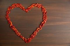以心脏的形式辣椒粉红辣椒 在木背景的纹理 日s华伦泰 免版税库存图片