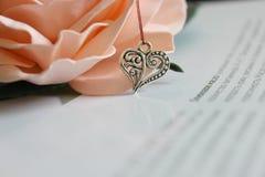 以心脏的形式银色垂饰在开花的背景上升了 库存照片