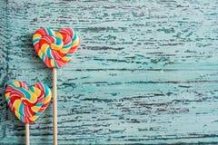 以心脏的形式,两上色了在棍子的镶边彩虹糖果 在蓝色老葡萄酒木背景 谷的概念 库存照片