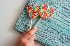 以心脏的形式,两上色了在棍子的镶边彩虹糖果 在蓝色老葡萄酒木背景 谷的概念 库存图片