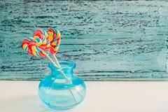 以心脏的形式,两上色了在棍子的镶边彩虹糖果 在蓝色老葡萄酒木背景 谷的概念 免版税库存照片