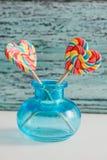 以心脏的形式,两上色了在棍子的镶边彩虹糖果 在蓝色老葡萄酒木背景 谷的概念 免版税库存图片