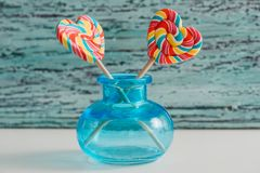 以心脏的形式,两上色了在棍子的镶边彩虹糖果 在蓝色老葡萄酒木背景 谷的概念 图库摄影