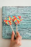 以心脏的形式,两上色了在棍子的镶边彩虹糖果 在蓝色葡萄酒木背景 Valentin的概念 库存图片