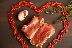 以心脏的形式,炽热胡椒被排行 麝香草分支,一瓣大蒜 由手工制造黑麦面包和t做的三明治 图库摄影