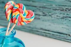 以心脏的形式,甜点上色了在棍子的镶边彩虹糖果 在老葡萄酒木背景 瓦伦蒂的概念 免版税库存照片