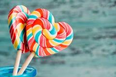以心脏的形式,甜点上色了在棍子的镶边彩虹糖果 在老葡萄酒木背景 瓦伦蒂的概念 免版税图库摄影