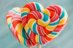 以心脏的形式,甜点上色了在棍子的镶边彩虹糖果 在老葡萄酒木背景 瓦伦蒂的概念 免版税库存图片