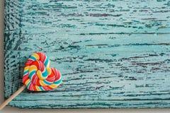 以心脏的形式,甜点上色了在棍子的镶边彩虹糖果 在蓝绿色老葡萄酒木背景 作为背景诱饵概念美元灰色吊异常分支 库存图片