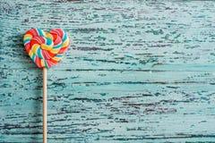 以心脏的形式,甜点上色了在棍子的镶边彩虹糖果 在蓝绿色老葡萄酒木背景 作为背景诱饵概念美元灰色吊异常分支 免版税库存照片