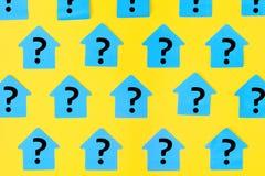 以房子的形式贴纸明亮的黄色背景的 在蓝色稠粘的笔记问号写道 免版税库存照片