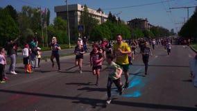 以橄榄球跑的三个球员,美式足球的形式 很多人,孩子跑沿路的一场马拉松 股票录像