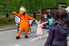 以橙色鸟,渡渡鸟比萨店比萨的标志的形式一个大玩偶,拍摄与节日的孩子 库存图片