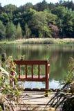 以湖为目的空的长凳在森林里,开始秋天 库存图片
