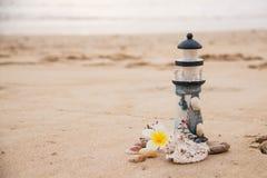以灯塔的形式美丽的在沙子的装饰和贝壳与文本的空间 库存图片
