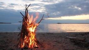 以烧在日落的河岸的帐篷的形式篝火 影视素材