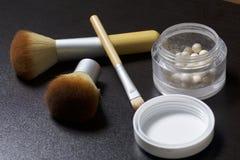以球的形式金黄轮廓色_在一个开放瓶子 接近应用的化妆用品刷子 项目符号 免版税库存照片