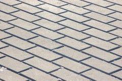 以砖,灰色铺路板的形式背景 在地面上的单调灰色砖石头街道路的 免版税库存照片