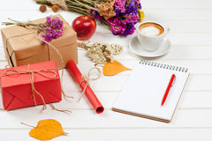 以秋天主题的工艺品礼物盒,装饰的黄色叶子,花 一个有铅笔的杯子热奶咖啡和笔记本 免版税库存图片