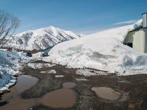 以积雪的小山和锡为目的春天风景 免版税库存图片