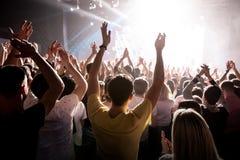 以纪念一个音乐展示的被举的手在阶段 免版税图库摄影