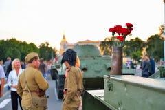以罐车的形式战士和在枪c的红色康乃馨 免版税图库摄影