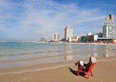 以色列人沿特拉唯夫海滩坐并且读了 库存照片