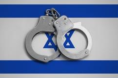 以色列旗子和警察手铐 法律在国家和保护的遵守的概念免受罪行 库存照片