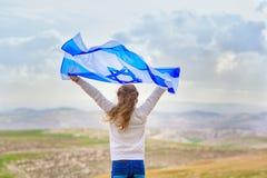 以色列犹太女孩有以色列旗子后面视图 免版税库存图片