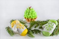 以说谎在一棵圣诞树的绿色分支的手套的形式两个蛋糕圣诞节的 复制空间 特写镜头 免版税图库摄影