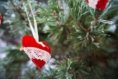 以透明球,毛毡的心脏的形式在圣诞树积雪的分支,圣诞节装饰垂悬 免版税库存照片