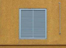 以透气格栅的形式,一个窗口在一个大工业购物中心关闭了与外在百叶窗 橙黄bei 库存照片
