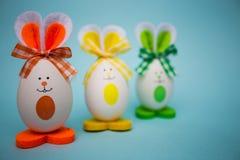 以逗人喜爱的兔宝宝的形式多彩多姿的滑稽的鸡蛋在蓝色背景 库存图片