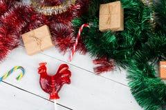 以雄鸡的形式糖果,礼物盒和圣诞节闪亮金属片下雨 免版税库存图片
