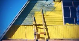 以黄色房屋涂料灰色,在那里墙壁附近是楼梯,但是修理过程暂停 免版税库存图片