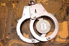 以黄色计算机为背景插件板是在警察钢手铐的一枚真正的bitcoin硬币 V的概念 免版税库存图片
