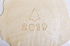 以2019年的形式在未加工的面团,题字,印从饼干的模子 来临的标志2019年 免版税库存图片