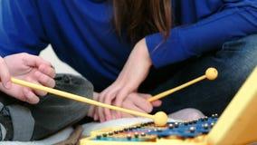 仪器音乐使用 特写镜头男孩、s手用使用在木琴的棍子和他的坐在他附近的老师 影视素材