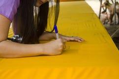 仪式优点传统泰国妇女在大一揽子黄色长袍写名字给盖子chedi 库存照片