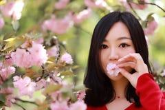 任意感觉本质上的自由愉快的妇女在室外春天的夏天,与在mounth的花 免版税库存照片