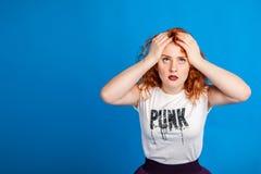 仿照低劣的情感概念样式的迷茫和恼怒的红头发人女孩 在明亮地蓝色m背景 安置文本 库存图片