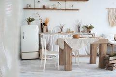 仿照破旧样式的白色织地不很细厨房 在一个生态样式和顶楼样式的一张大桌 土气架子,餐巾,老r 免版税库存图片