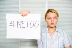 仿造妇女哀伤的面孔举行海报的hashtag 性攻击和骚扰的受害者在工作场所 保护女性 免版税图库摄影