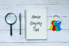 企业、财务和物产概念 放大镜、笔、钥匙和笔记本顶视图写与议院购买技巧 库存图片