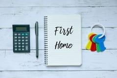 企业、财务和物产概念 计算器、笔、钥匙和笔记本顶视图写与第一个家 库存图片